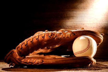 guante de beisbol: Viejo béisbol de cuero desgastado receptor del deporte del guante y la pelota cosida edad en los tablones de madera antiguos en la luz suave nostalgia Americana