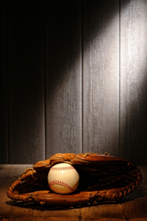 Vintage sport ball in an old baseball catcher leather glove on aged wood planks in an antique stadium dugout