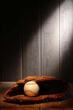 guante de beisbol: Bola de deporte de la vendimia en un guante de cuero viejo b�isbol receptor de tablones de madera de edad en una antigua caseta del estadio