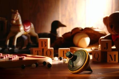 juguetes antiguos: Nostálgico de juguetes antiguos de madera girando la parte superior el tiempo de juego y la recolección tradicional de Niños de madera juguetes con guante de béisbol y un oso de peluche con los bloques de madera y mármoles antiguos en un ático iluminado por la luz solar difusa suave