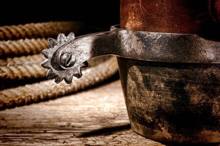 rodeo americano: American West Rodeo Cowboy tradicional de cuero con el tac�n de la bota Roper espuela aut�ntica monta western y lazo sobre la madera de la vendimia en un cobertizo de las antig�edades de cr�a en granjas Foto de archivo