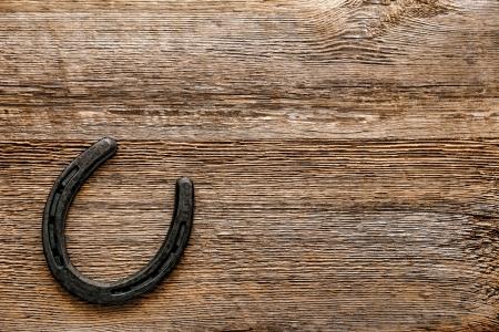 herradura: Hierro viejo en metal fundido y occidental caballo herrado accesorio de herradura en el fondo antiguo resistido tablón de madera Foto de archivo