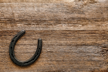 Old cast iron metal Western horse shoeing accessory horseshoe on antique weathered wood plank background  Stok Fotoğraf
