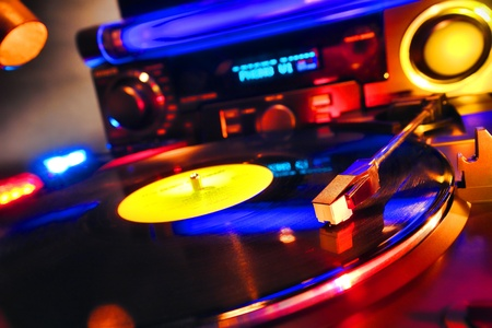 Vinyl record playing hot techno music on an audio DJ turntable photo