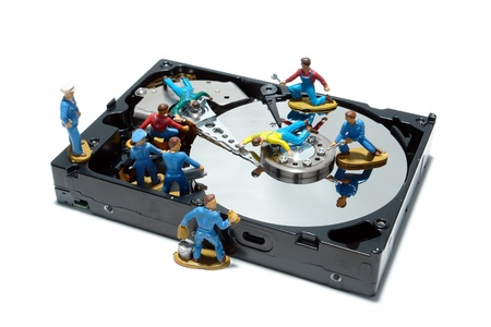 computer repair technician: Open computer hard disc drive hardware component with miniature toy figurines service station mechanics over white as concept illustration for proper maintenance (1 in a series of 6) Stock Photo