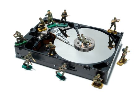 hard drive: Open computer hard disc drive hardware component with miniature toy figurines army soldiers white as concept illustration for virus and malware protection (1 in a series of 6) Stock Photo