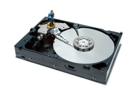 hard drive: Open computer hard disc drive hardware component with miniature toy figurine professional photographer over white as concept illustration for regular backup (1 in a series of 6) Stock Photo