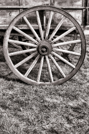 Old American pioneer prairie schooner wagon antique wood spoke wheel over prairie grass  Stock Photo - 14623915