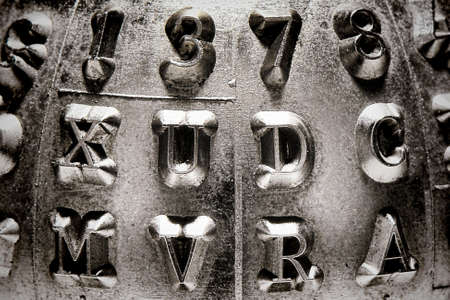 serif: Stamped metal numbers and capital serif letters abstract grunge background
