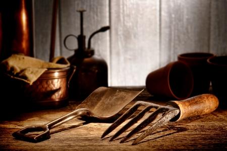 spading fork: Vintage gardening tools steel spading fork and metal shovel on aged wood potting table in an old antique garden shed
