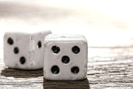 Antique bone craps game and wager gambling lucky shooting dice on old weathered wood table