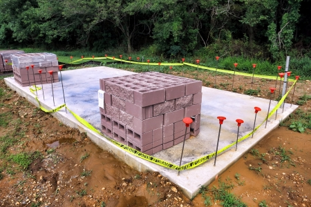 Stack of new masonry cinder blocks ready for wall assembly on a poured concrete slab footing surrounded by mud at a building construction site photo