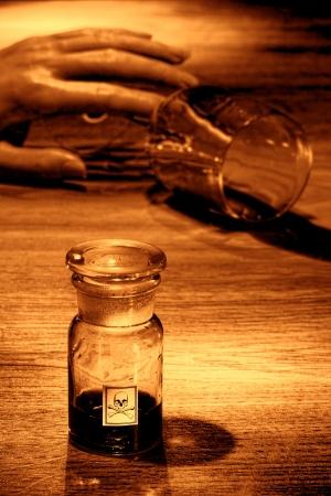 veneno frasco: Escena del crimen horripilante asesinato de una mano muerta sosteniendo un vaso de agua derramado con veneno botella vac�a como evidencia criminal forense en sepia grunge �spera