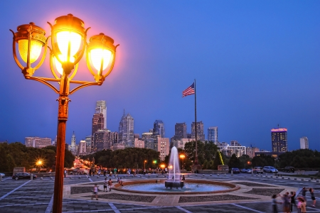 Downtown Philadelphia Center City scenic cityscape skyline with Benjamin Franklin Parkway and lit streetlight post from Museum of Art plaza with fountain at dusk Stock Photo