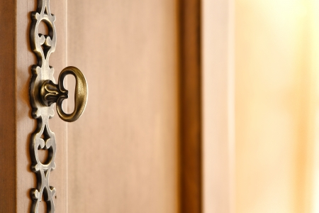Old traditional brown wood furniture decorative door key like handle aged bronze pull hardware on cabinet style armoire door Stock Photo - 14841659