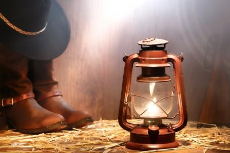 fusil de chasse: American West cowboy de rod�o vitesse avec un chapeau au sommet de cuir v�ritable moulinette bottes et lasso avec fusil de chasse antique �clair� par une lampe lampe � p�trole vintage et lumi�re douce diffus�e dans la fen�tre de la fum�e dans une grange en bois vieux ranch