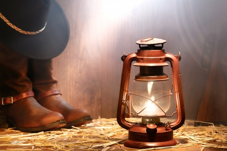 American West rodeo cowboy gear with hat atop authentic leather roping boots and lasso lariat with antique shotgun lit by a vintage kerosene lantern lamp and soft window light diffused in smoke in an old ranch wood barn photo