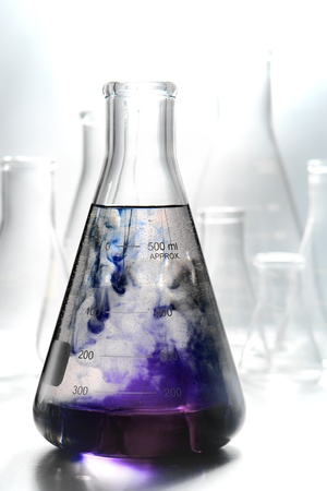 Scientific laboratory glass conical Erlenmeyer flask filled with swirling and reacting purple chemical liquid mix in a reaction for a chemistry experiment in a science research lab Stok Fotoğraf