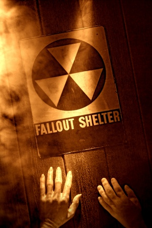 refuge: Gruesome and tragic nuclear disaster catastrophe scene with dead victims hands reaching for emergency fallout shelter sign in fire smoke in rough grunge sepia Stock Photo