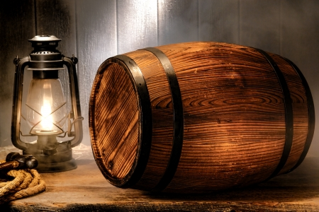 kerosene lamp: Old wood antique whisky wood barrel or rustic wine keg container with vintage kerosene lamp light lantern in smoke like fog in a smoky nostalgic American waterfront port wooden warehouse