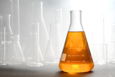 material de vidrio: Científicos de laboratorio de cristal erlenmeyer cónico lleno de líquido ambarino anaranjado química con el equipo de cristalería en la niebla o el humo de un experimento de química en un laboratorio de investigación en ciencias Foto de archivo