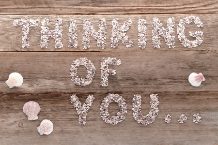 The love and feelings sentence thinking of you in words written in small pebbles letters as a message on old aged weathered wood planks background Stock Photo - 15012628