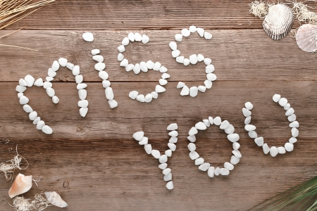 The love and feelings sentence miss you in words written in small pebbles letters as a message on old aged weathered wood planks background
