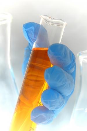 Científico mano que sostiene un cilindro científico Foto de archivo - 15168038
