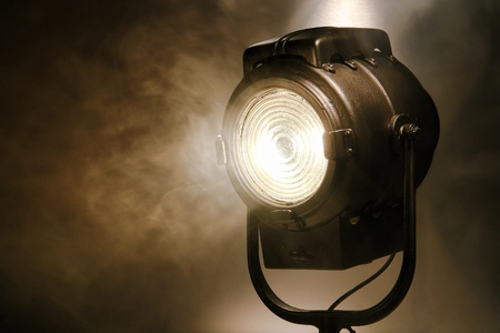 Hollywood old movie studio vintage Fresnel style halogen hot spot light in smoke in sepia photo