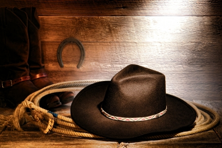 American West rodeo cowboy black felt hat on an authentic Western roping lariat lasso with leather riding boots on weathered wood floor in an old ranch barn Stok Fotoğraf