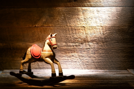 Nostalgic Americana scene of an antique reproduction wood toy rocking horse on aged wooden plank floor in a dusty old house attic lit by soft diffused sunlight through a window