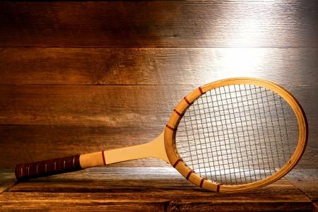 raqueta de tenis: Raqueta de tenis de madera de la vendimia en el piso viejo tablón de madera en una vieja casa desván polvoriento iluminado por la luz solar difusa y suave a través de una ventana