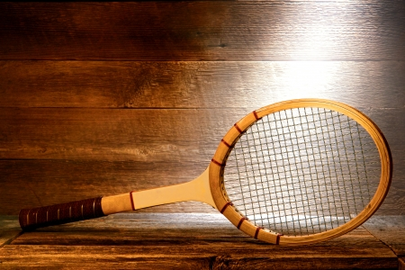 attic: Vintage wood tennis racket on aged wooden plank floor in a dusty old house attic lit by soft diffused sunlight through a window