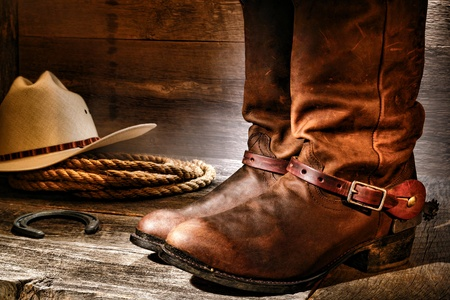 rodeo americano: American West rodeo vaquero par de cuero tradicional Roper estilo occidental botas de montar con espuelas auténticos ganaderas con el sombrero y la cuerda en un piso de madera antigua en un rancho viejo granero de madera envejecido