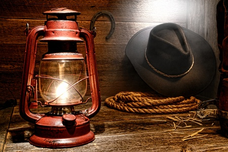 Vintage kerosene lantern lamp illuminating American West rodeo cowboy gear with hat and ranching lasso rope with spurs on authentic leather roping boots and soft window light diffused in smoke in an old ranch wood barn photo