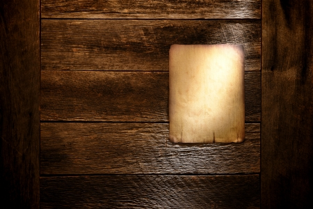 Old blank parchment paper western poster board notice with empty copy space display on aged and weathered barn wood wall background in grunge light photo