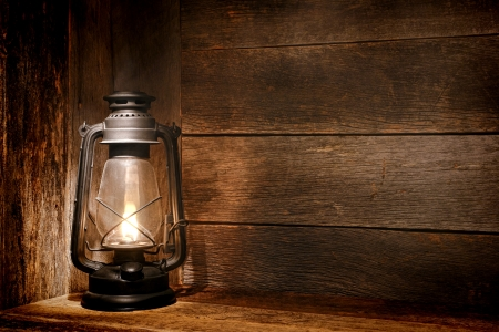 Old fashioned vintage kerosene oil lantern lamp burning with a soft glow light in an antique rustic country barn with aged wood wall and weathered wooden floor photo