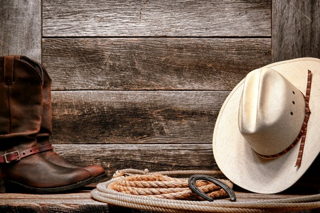 American West rodeo traditional white straw cowboy hat with authentic Western lariat lasso and roper leather boots on distressed barn wood background photo