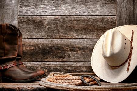 american rodeo: West americano rodeo tradizionale cappello bianco da cowboy di paglia con autentica occidentale lazo lariat e Roper stivali di pelle su sfondo afflitto legno fienile