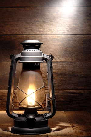 Old fashioned rustic kerosene oil lantern lamp burning with a soft glow light photo