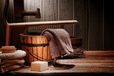 Antique laundry manual wash scene with old towels and ancient natural soap bar near vintage wood bucket  Stock Photo