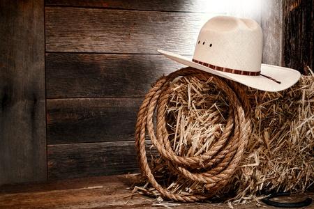 american rodeo: West americano rodeo cowboy cappello di paglia bianco con corda tradizionale occidentale di bestiame su una balla di fieno in un vecchio fienile ranch in legno illuminato da luce diffusa