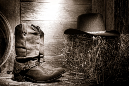 barn boots: American West rodeo authentic leather roper boots and traditional western black felt hat on a bale of straw hay in an old wood ranch barn lit by diffused light Stock Photo