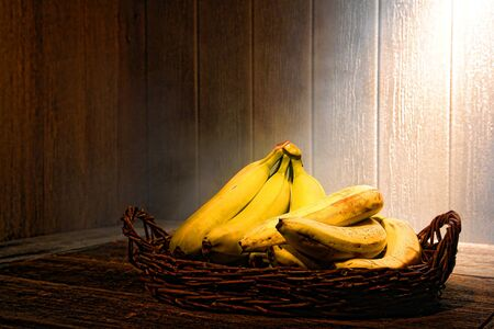 Fresh ripe bananas fruits in an ancient wicker basket on an old wood table in the vintage kitchen of an antique home Stock Photo - 16762785
