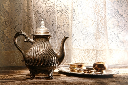 Old antique silver teapot and traditional tea serving accessories on an ancient tray on an ancient wood table with vintage lace window curtain in a historic home Stok Fotoğraf