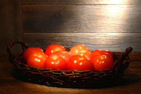 diffused: Organic fresh tomatoes in an old wicker basket on a traditional country farm produce stand wood table in a vintage rural barn lit by soft diffused sunlight