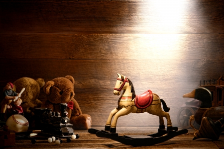 attic: Vintage rocking horse toy and forgotten antique wood play toys reproductions with teddy bears in an old historic house ancient wood attic lit by soft dusty and hazy light Stock Photo