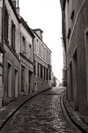 incline: Small and narrow village cobblestone paved street with traditional French city houses in an incline hill downtown area in France
