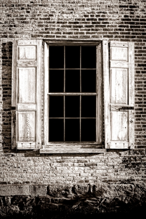 colonial: Old antique window with ancient glass panes and broken wood shutters on aged brick wall on an abandoned historic home colonial building