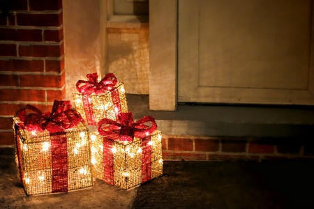 Lighted decorated Christmas gift boxes with red bows and festive inside lights at a house doorway front door for cheerful holyday decor